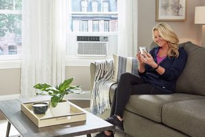Woman in living room with control to smart air conditioner