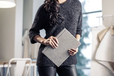 A woman holding a Surface Pro 7 with a Type Cover.