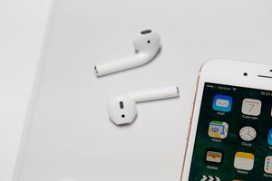A set of Apple AirPods lying next to an iPhone