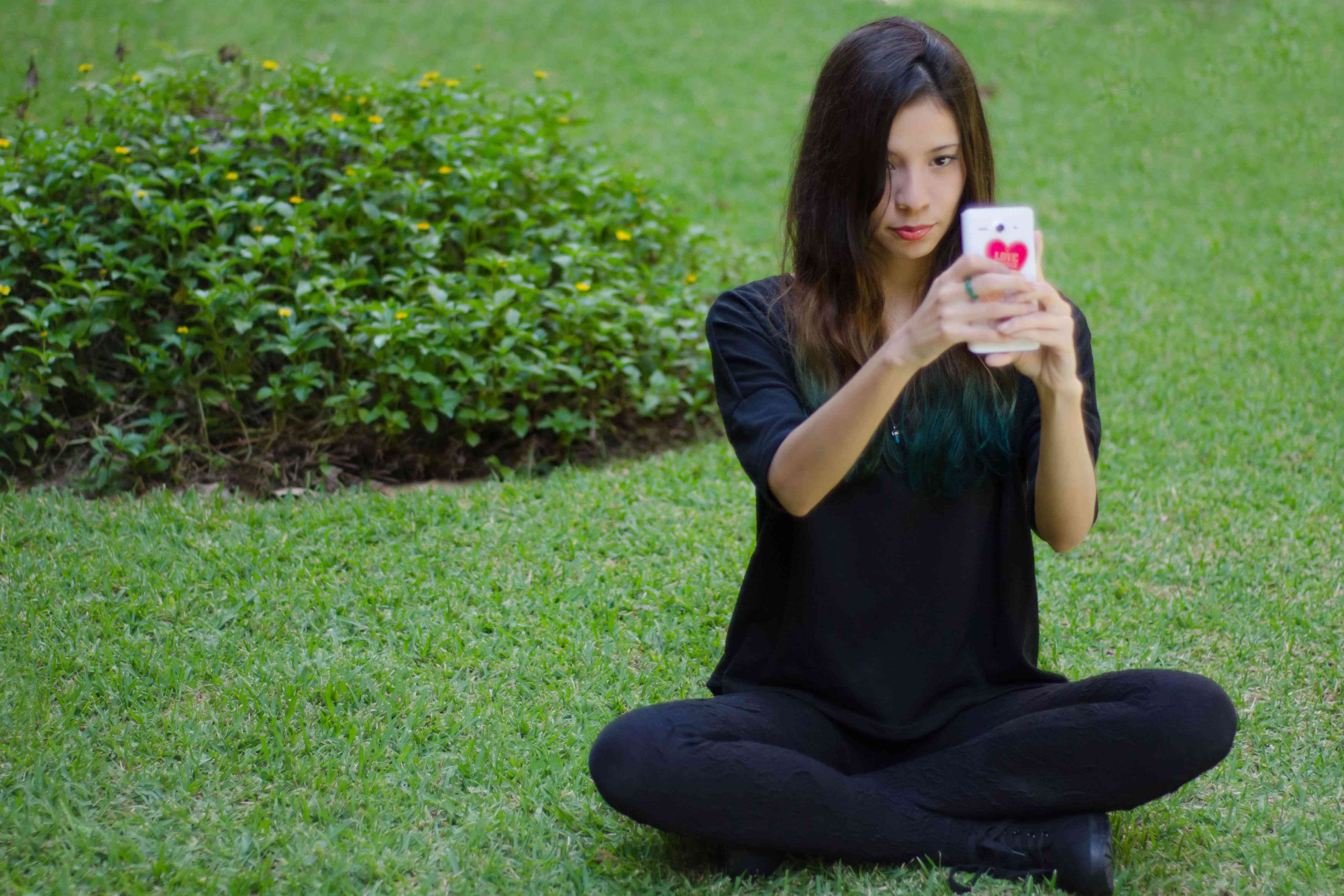 A person sitting on the grass using a cellphone
