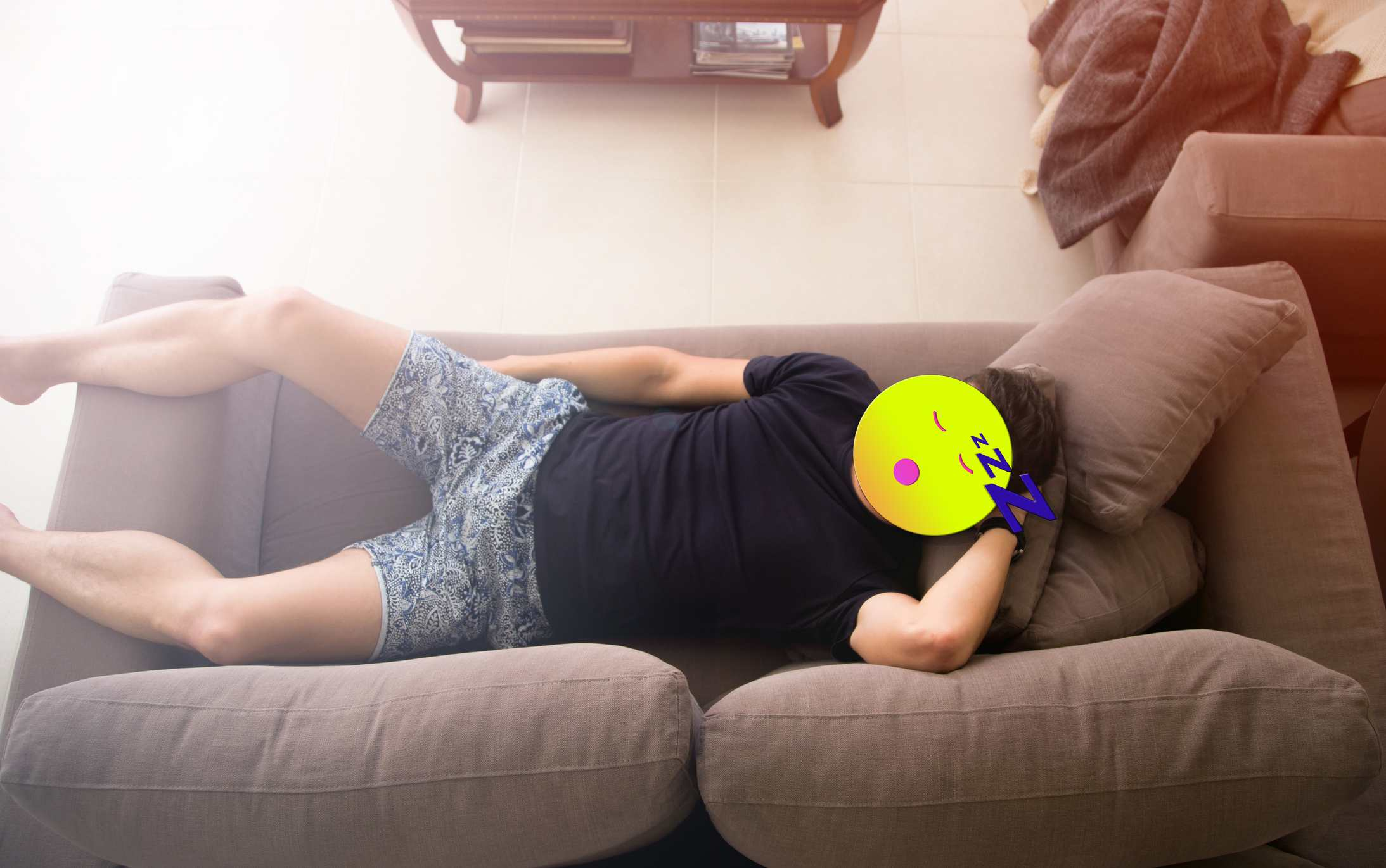 A man lying on a couch with an emoji in front of his head