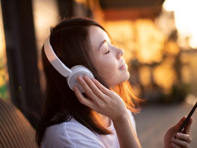 A woman sitting with her eyes closed with headphones on and holding a smartphone