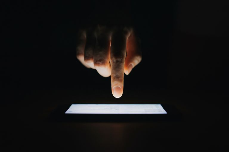 A hand above an iphone about to touch with a single finger