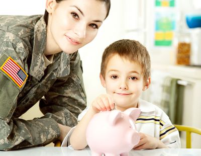 Female soldier with son dropping coins into pink piggy bank.