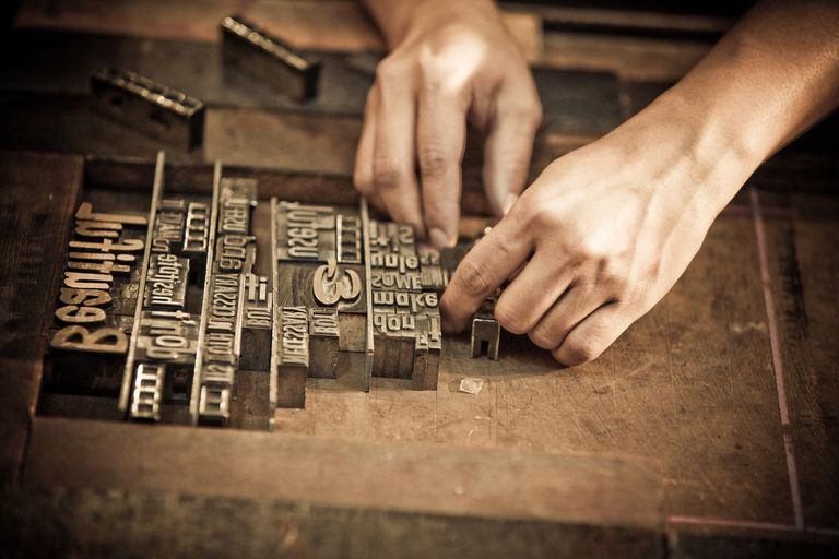 A pair of hands arrange letters for letterpress