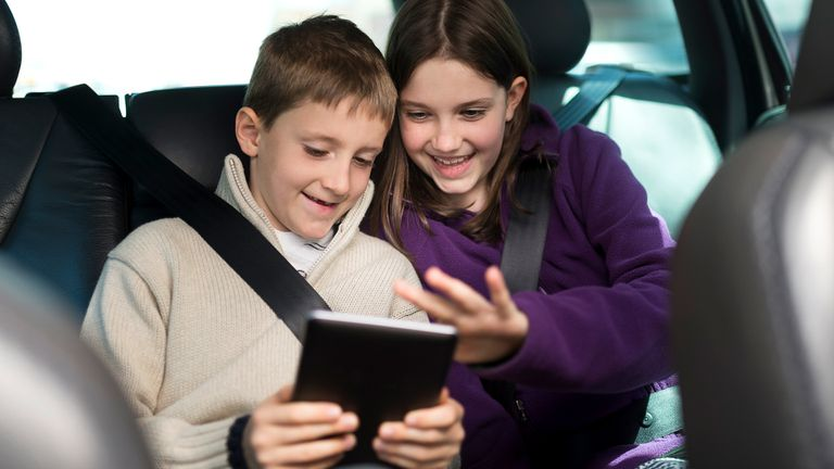 A boy and girl playing offline video games on their Android tablet in the back seat of a car.