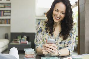 Interior designer using smart phone in home office