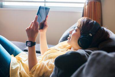Woman wearing headphones using tablet