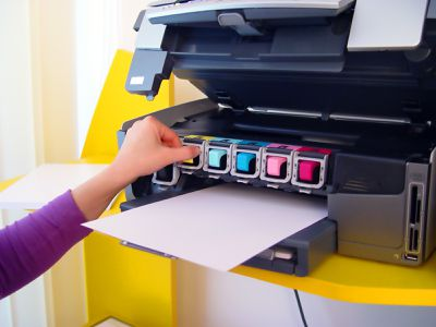 Someone changing out the ink in a printer.