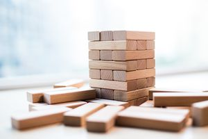 A tall stack of wood Jenga blocks on a white table