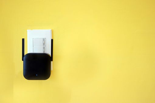 Close-Up Of Wi-Fi Extender Against Yellow Wall