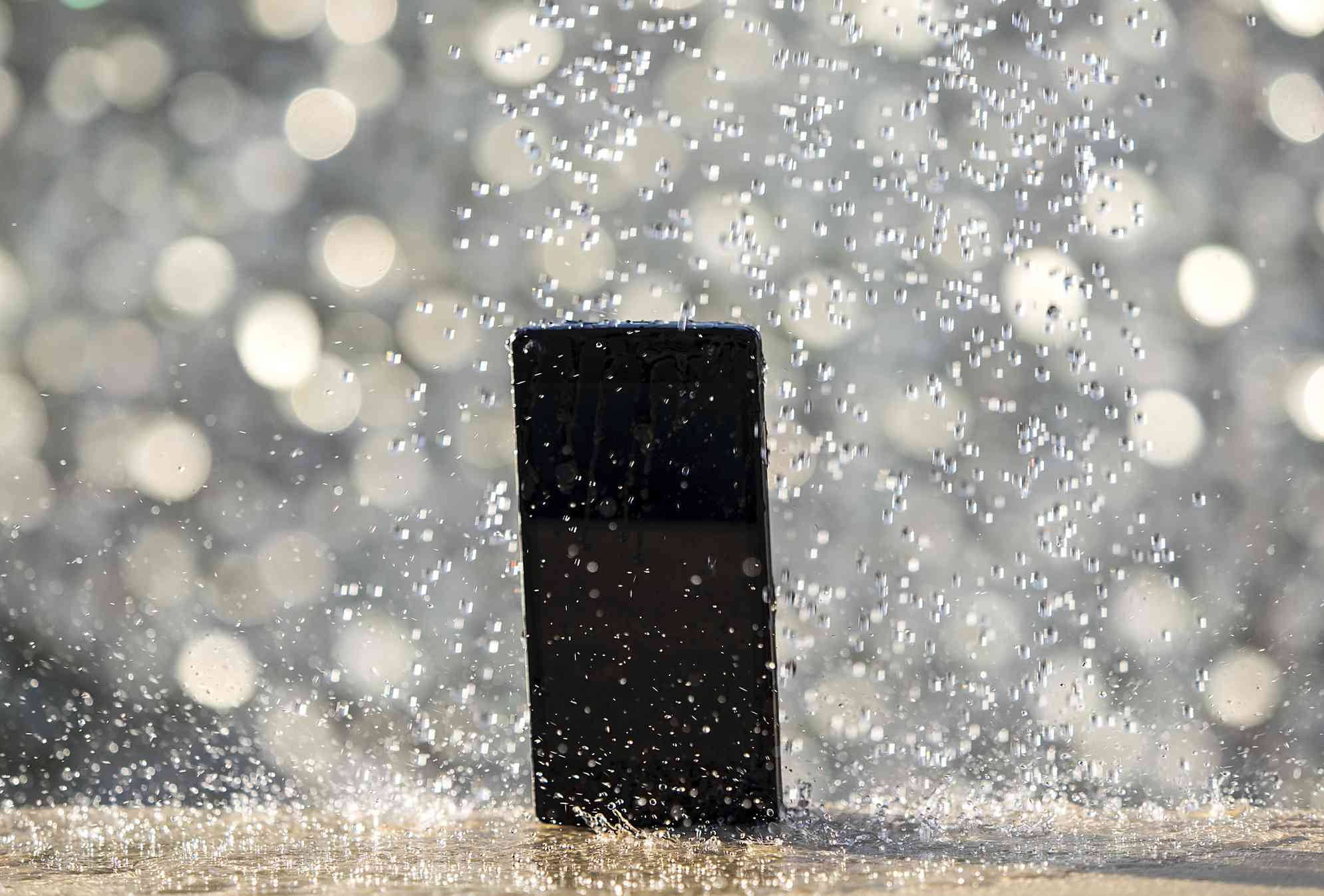 iPhone getting soaked by a torrent of water droplets