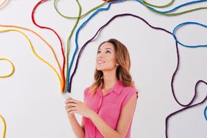 A woman holding a mobile phone with rainbow colors coming out of it.