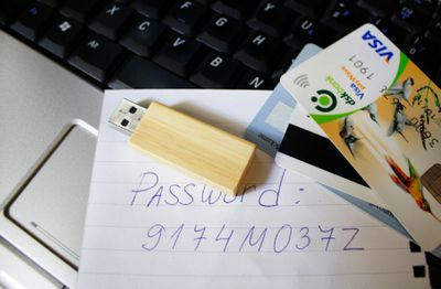 Credit cards and a thumb drive sitting on a laptop with a password written on paper.