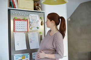 Pregnant woman looking at calendar on fridge