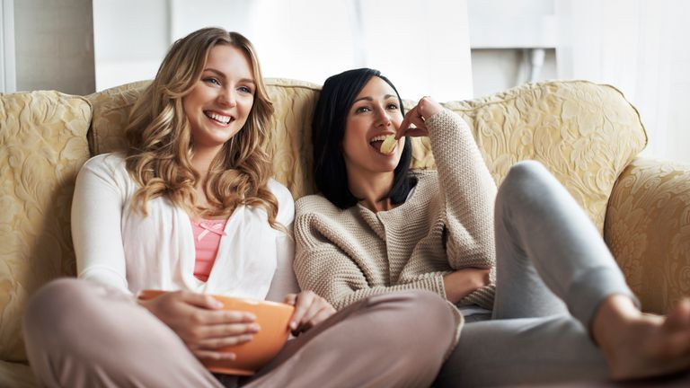 Two women watching TV on their Xbox One console and controlling it with Microsoft's Cortana virtual assistant