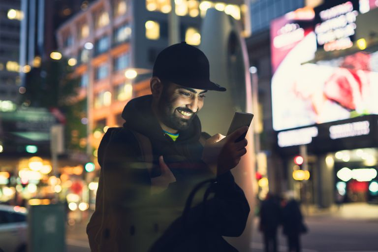 Man using a smartphone at night in well-lit city square