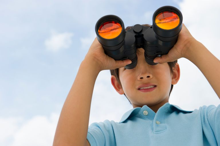 Mixed race boy looking through binoculars