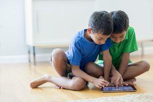 Boys using digital tablet on floor