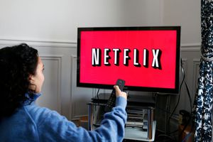 A person sitting in front a TV that displays the Netflix logo.