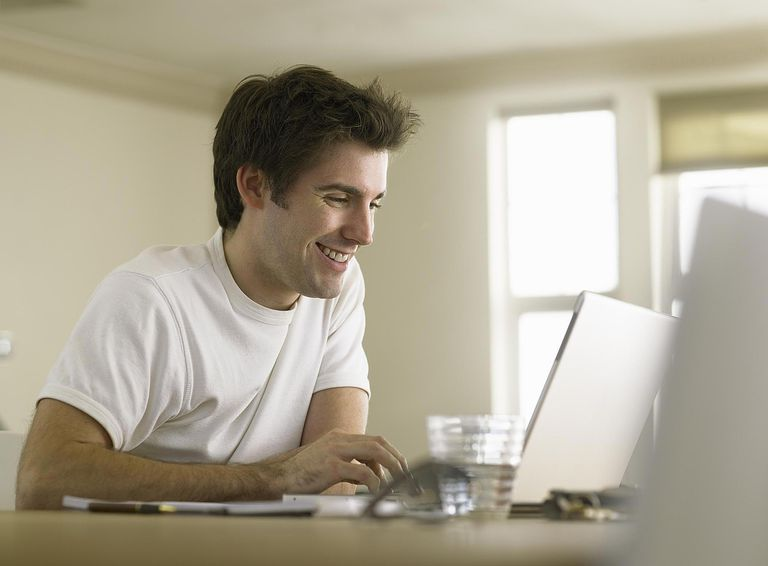 Young man using laptop at home, smiling
