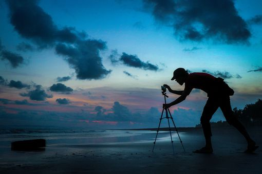 Silhouette Man Adjusting Mobile Phone On Tripod At Shore Against Cloudy Sky