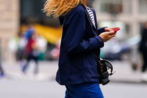 Woman walking holding a mobile phone