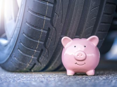 Pink piggy bank in front of a car tire.