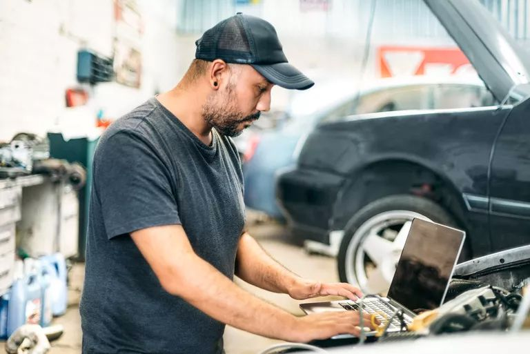Auto technician with computer connected to car