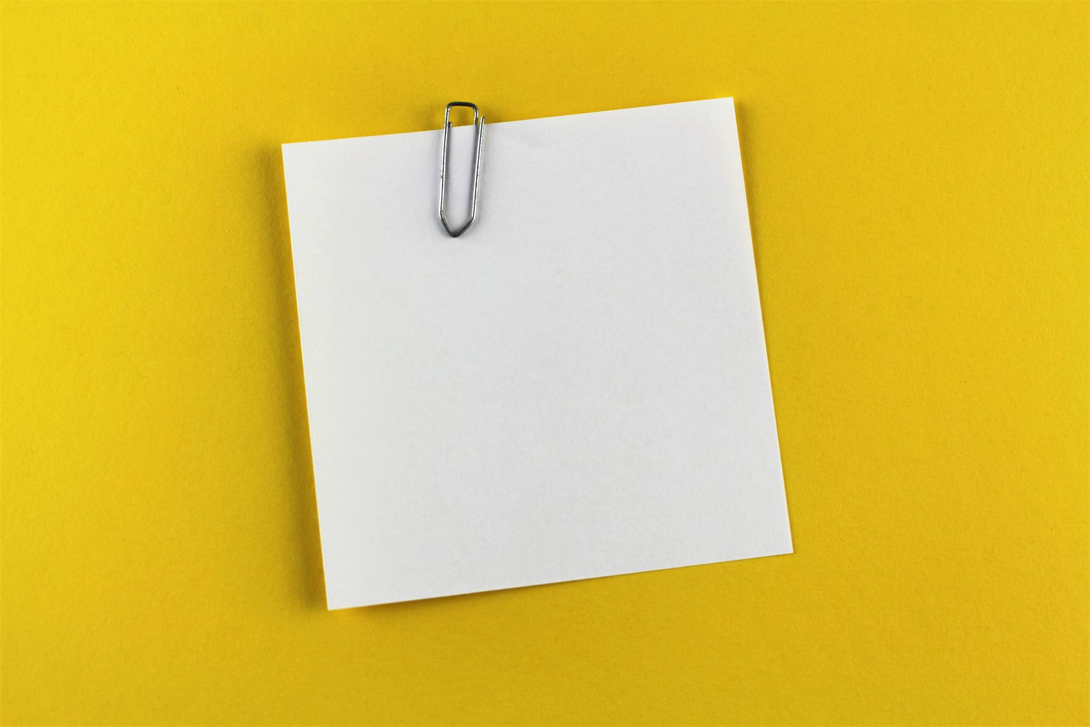 Close-Up Of Empty Paper Hanging On Yellow Background with Paperclip Attachment