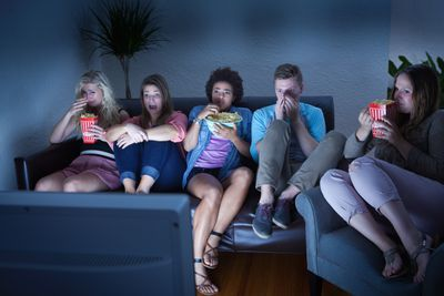 People watching a movie at home. With popped corn.