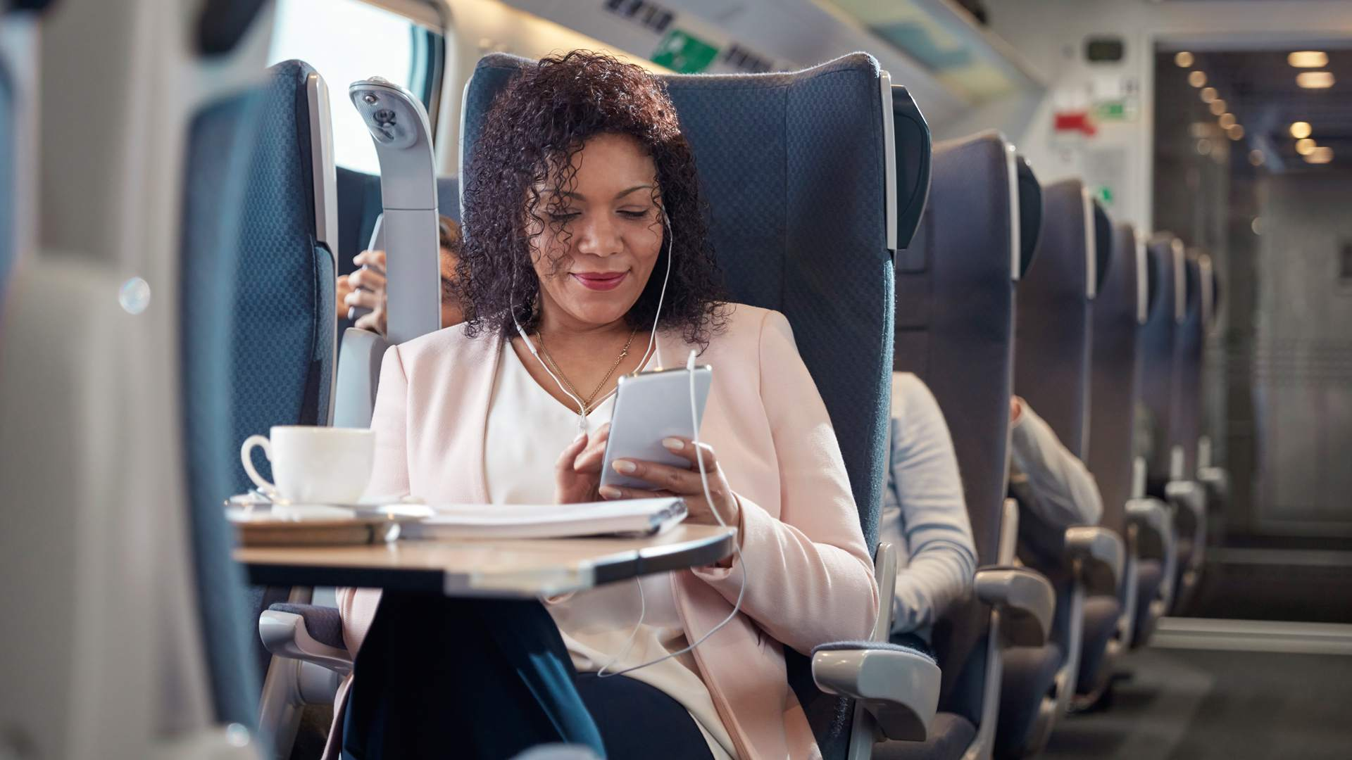 A woman watching downloaded videos on her smartphone while traveling internationally.