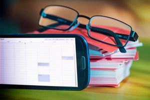 Smart phone with calender on display, memos and reading glasses in background