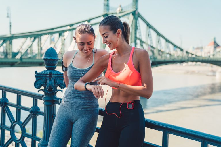 Two women runners resting, looking at their fitness trackers