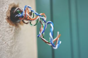 A tangle of colored speaker wires coming through a hole in a wall