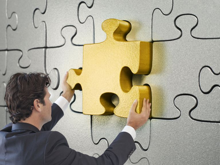 gold puzzle piece being inserted by a man in a silver puzzle piece wall