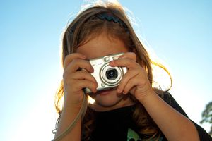 Child taking a photo with a point and shoot camera