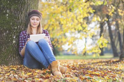 Young person in the park using a tablet PC to download free fall wallpaper