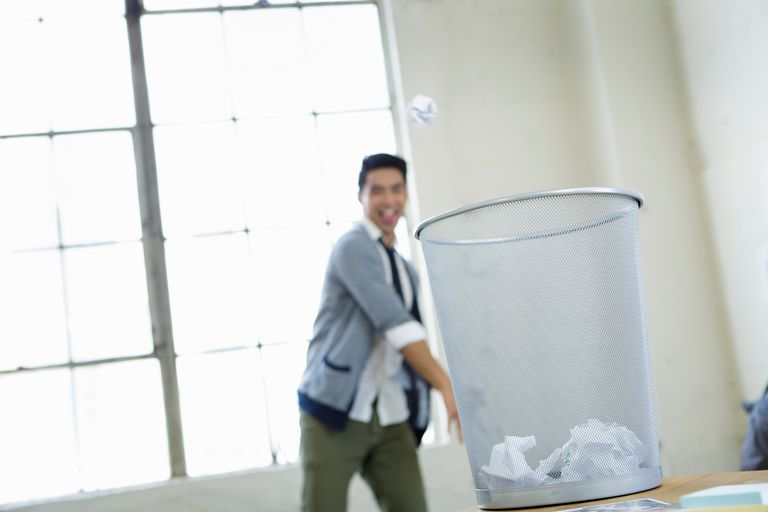 Young man in office throwing paper into wastepaper basket
