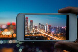 Photographer capturing a skyline using a smartphone