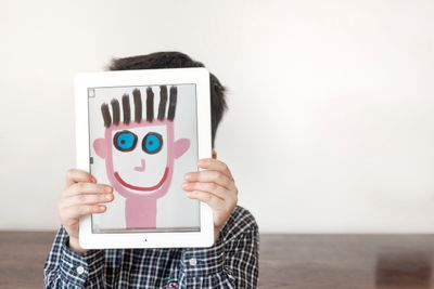 A child holding a tablet in front of their face with image of painted face.