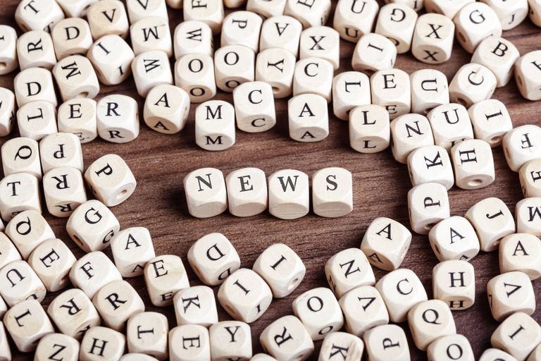 High Angle View Of News Text Arranged With Alphabet Blocks On Wooden Table