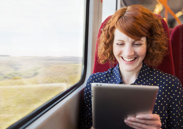 Woman using iPad on train