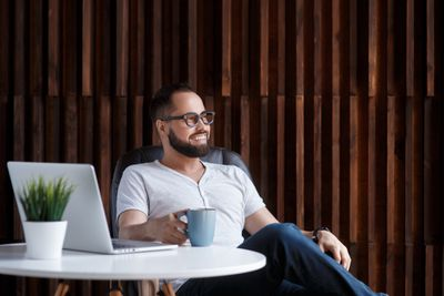 A man sitting at a desk holding a cup of coffee with a laptop at his side