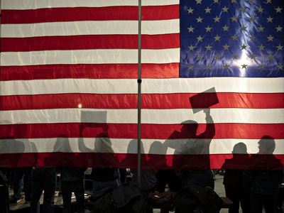 People Silhouetted Against An American Flag.