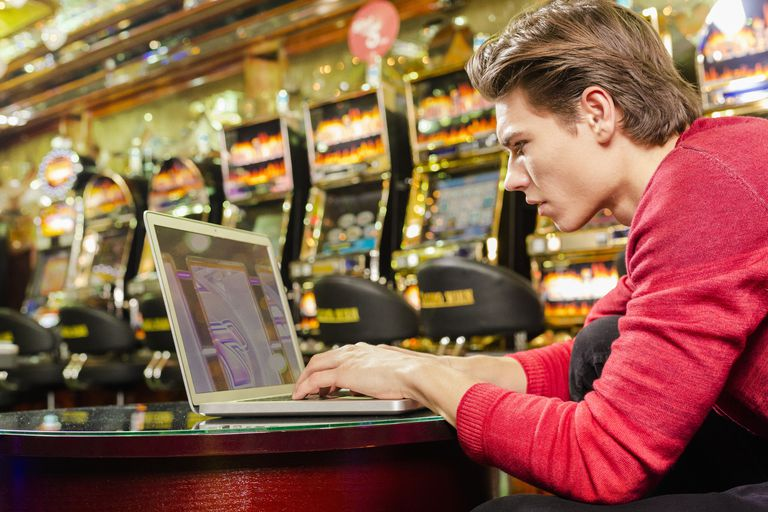 Young man playing poker on his laptop in a casino