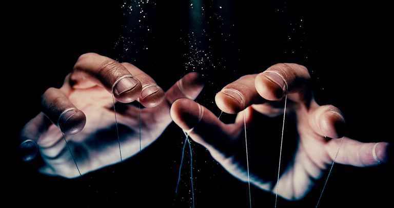 Close-Up Of Hand With String Against Black Background