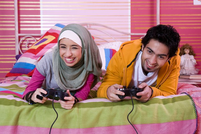 Two teenage brother and sister enoying playstation games in bed.