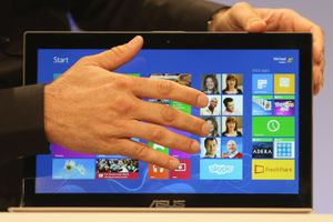 hand in front of the screen of a laptop running Microsoft Windows 8
