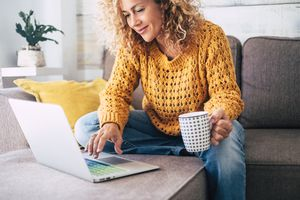 woman sitting on sofa working on computer